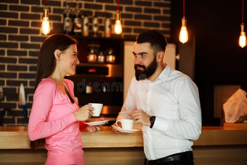 Les jeunes couples heureux se sont réunis la barre et en parlant avec la tasse de café images stock