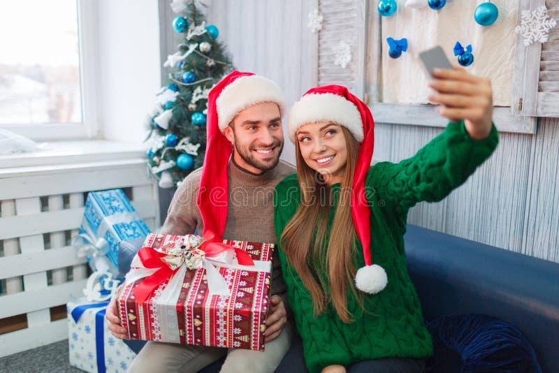 Les jeunes couples heureux souriant, font le selfie, homme tenant le boîte-cadeau dans des mains photos libres de droits