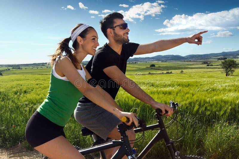 Les jeunes couples heureux sur un vélo montent dans la campagne image libre de droits