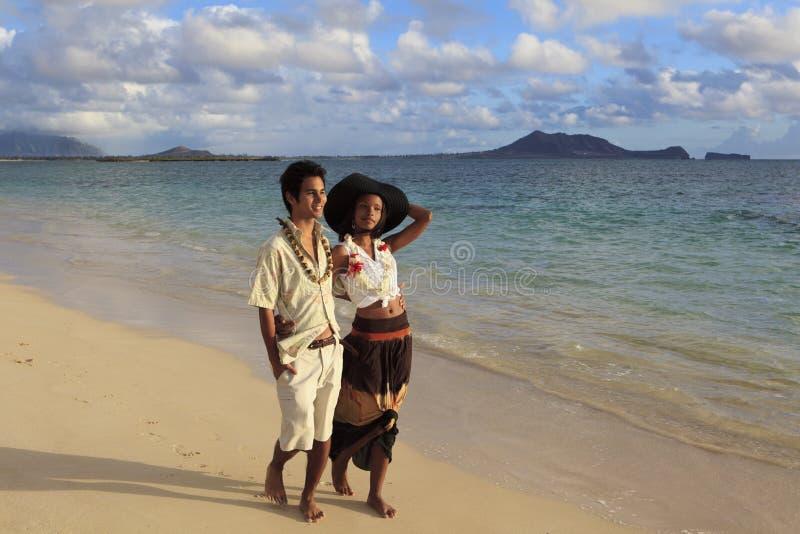 Les jeunes couples mélangés marchent sur une plage photo stock