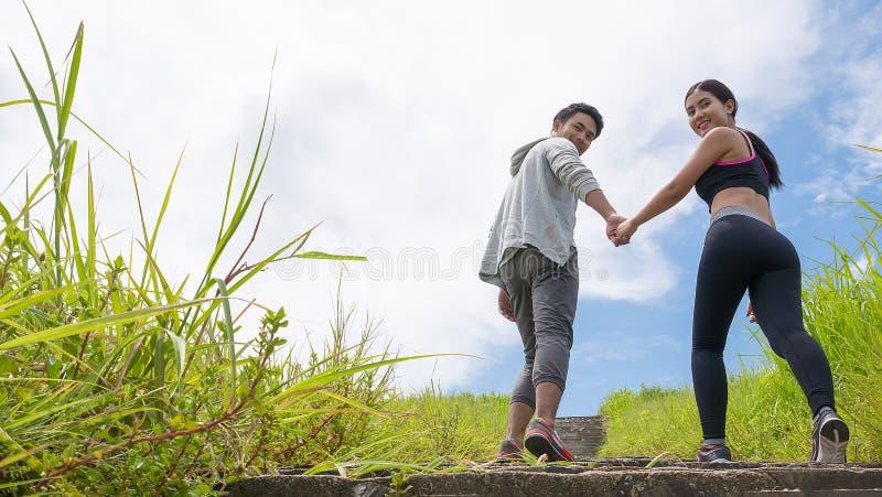 Les jeunes couples, main de participation d'amant intensifient l'escalier extérieur pour un concept de pulser, sain et d'exercice image libre de droits