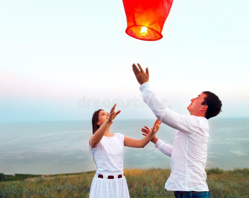 Les jeunes couples mettent en marche une lanterne chinoise rouge de ciel dans le crépuscule photos stock