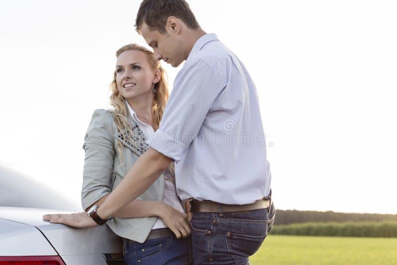 Les jeunes couples romantiques se penchant dessus soutiennent de la voiture à la campagne images stock