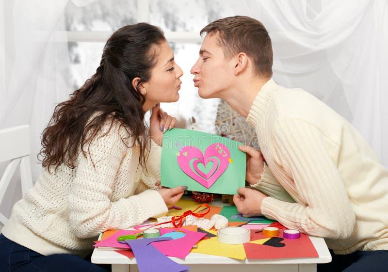 Les jeunes couples romantiques se reposent à la table et montrent à origami le coeur rouge, les personnes heureuses et le concept photo libre de droits