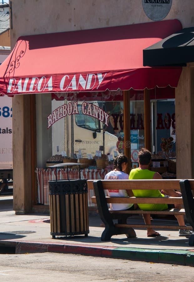 Les jeunes couples se reposent sur un banc sur le trottoir devant le magasin de bonbons de Balboa photos stock