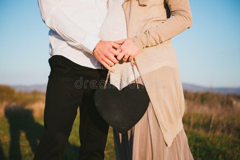 Les jeunes couples se sont occupés de l'enfant extérieur, tableau noir images stock