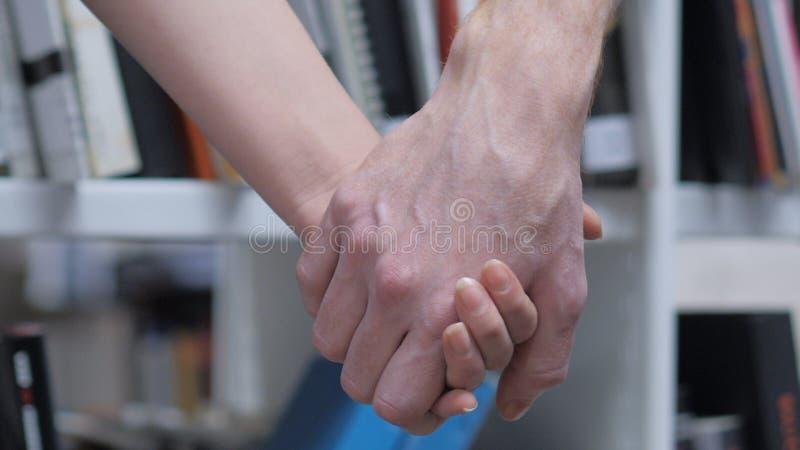 Les jeunes couples tenant la main de chacun dans l'amour, se ferment  photographie stock