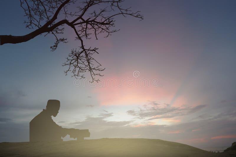 Les jeunes de musulmans prient pour la paix de koran de lecture de Dieu dans l'ea moyen photo stock