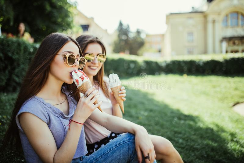 Les jeunes deux amies de femmes mangent la crème glacée se reposant sur l'herbe dans des rues de ville d'été photos stock