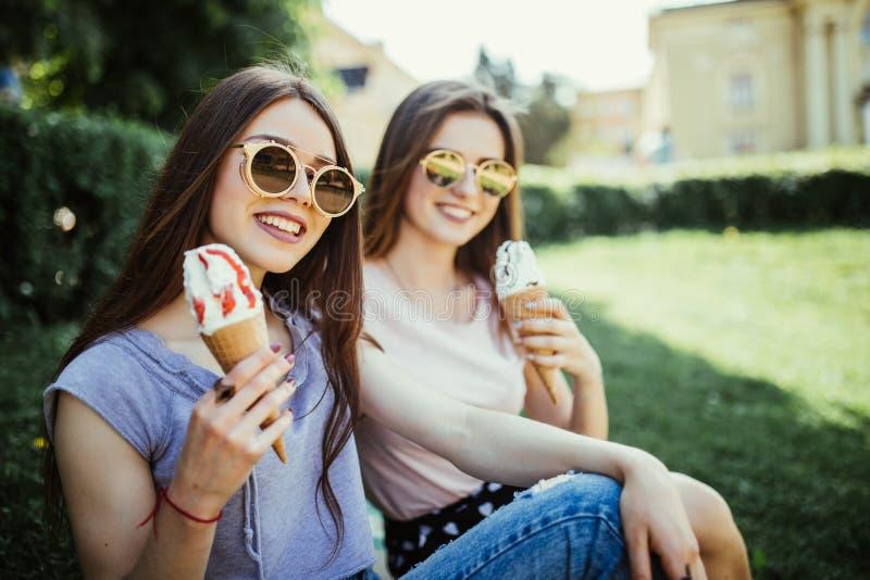 Les jeunes deux amies de femmes mangent la crème glacée se reposant sur l'herbe dans des rues de ville d'été images stock