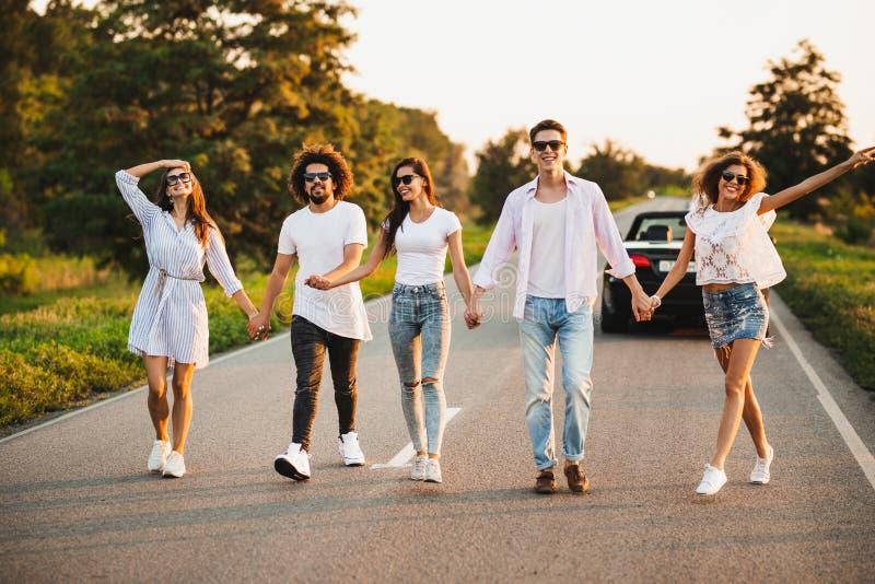 Les jeunes deux types élégants et trois filles tiennent des mains et marchent sur la route un jour ensoleillé image libre de droits