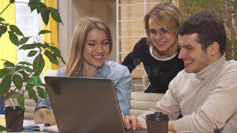 Les jeunes discutent un certain projet sur l'ordinateur portable images stock