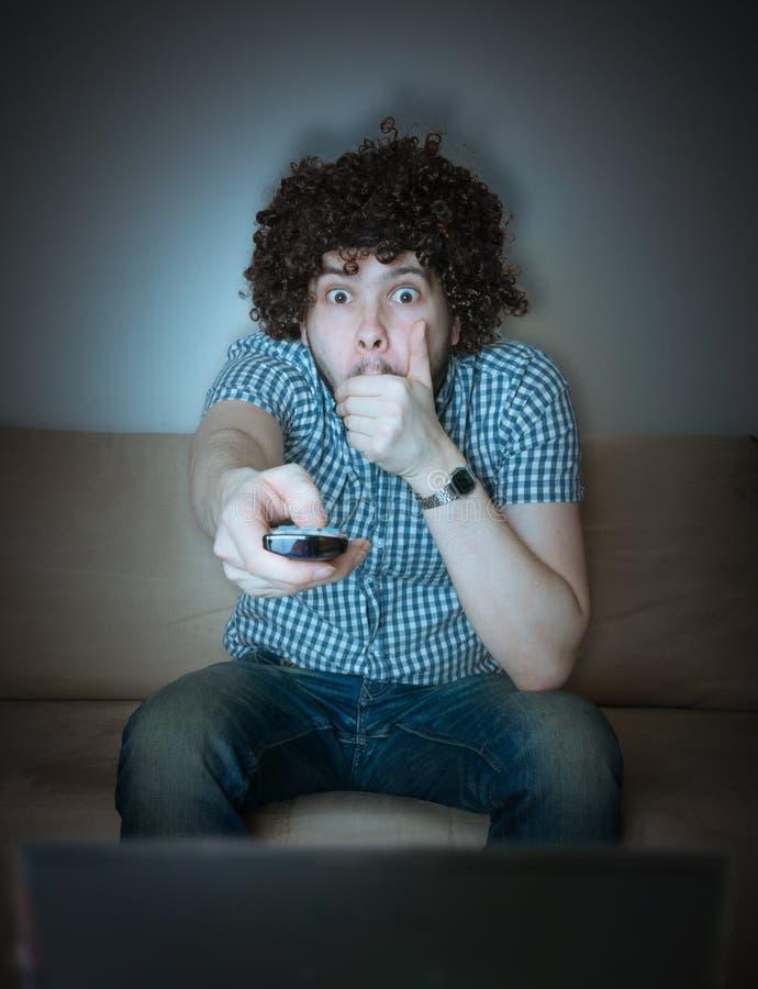 Les jeunes effrayés équipent observent l'horreur ou le thriller à la TV images libres de droits