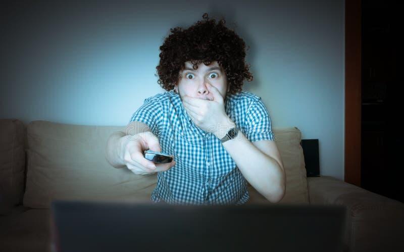 Les jeunes effrayés équipent observent l'horreur ou le thriller à la TV et jugent à télécommande photos stock
