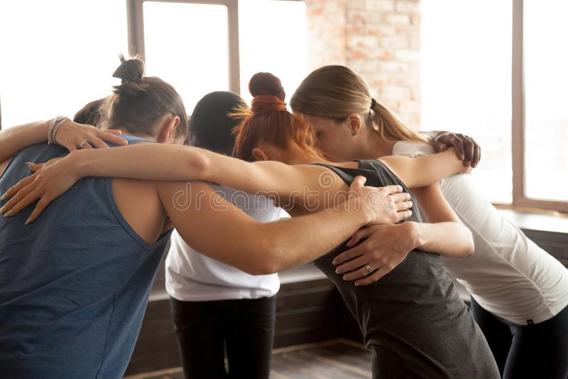 Les jeunes embrassant en cercle se tenant ensemble, unité de groupe photos libres de droits