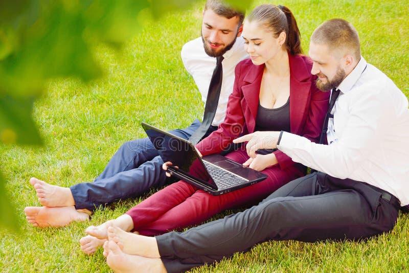 Les jeunes employés de bureau avec les pieds nus s'asseyent sur une pelouse verte avec un l images stock