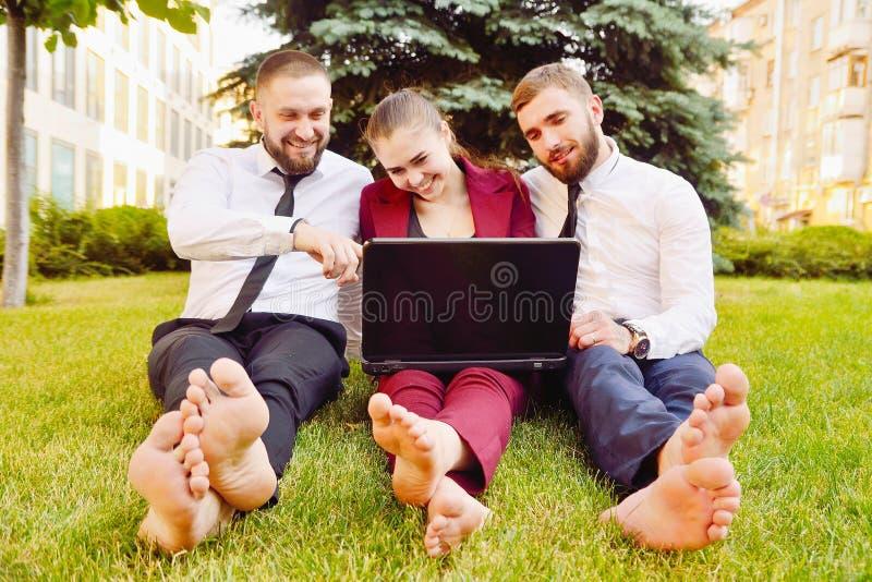 Les jeunes employés de bureau avec les pieds nus s'asseyent sur une pelouse verte avec un l photos stock