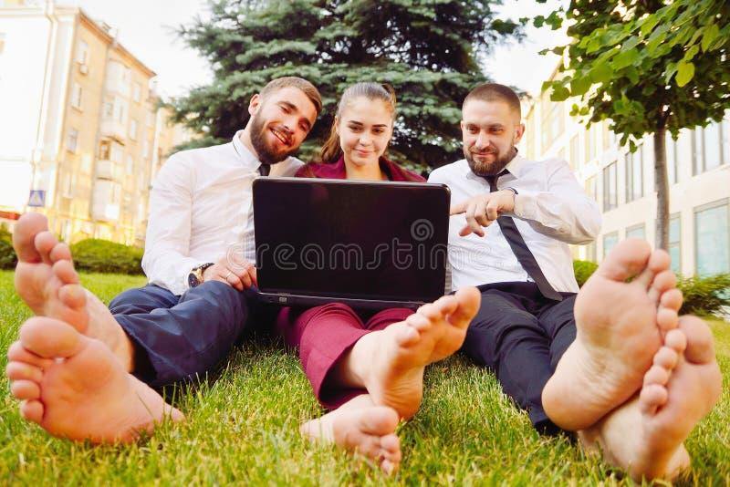 Les jeunes employés de bureau avec les pieds nus s'asseyent sur une pelouse verte avec un l photographie stock
