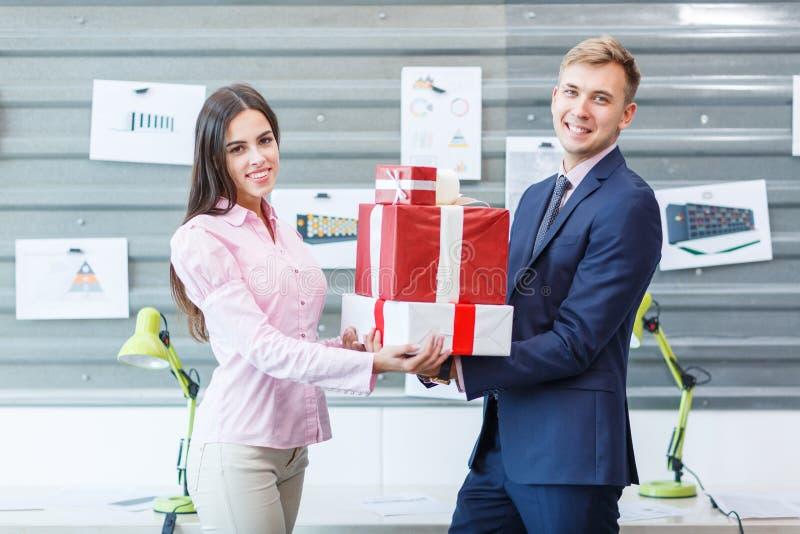 Les jeunes employés se tiennent avec des présents dans le bureau images stock