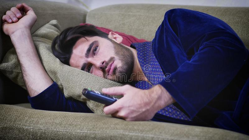 Les jeunes ennuyés équipent se reposer sur l'observation de sofa photos stock