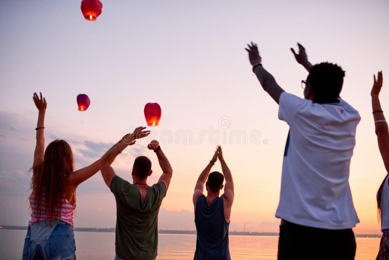 Les jeunes enthousiastes disant au revoir aux lanternes volantes de ciel photos stock