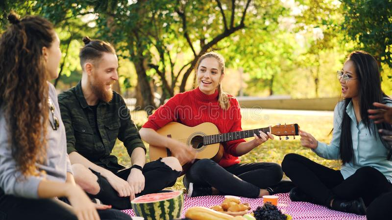 Les jeunes espiègles sont chantants et déplaçants des mains quand la belle fille joue la guitare pendant le pique-nique en parc d images stock