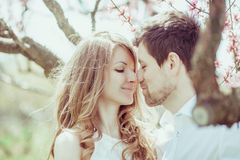Les jeunes et heureux nouveaux mariés sont les nez émouvants en parc de floraison Verticale extérieure de plan rapproché photographie stock