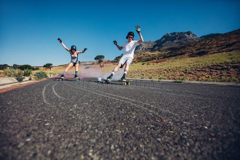 Les jeunes faisant de la planche à roulettes avec la bombe fumigène sur la route photo libre de droits