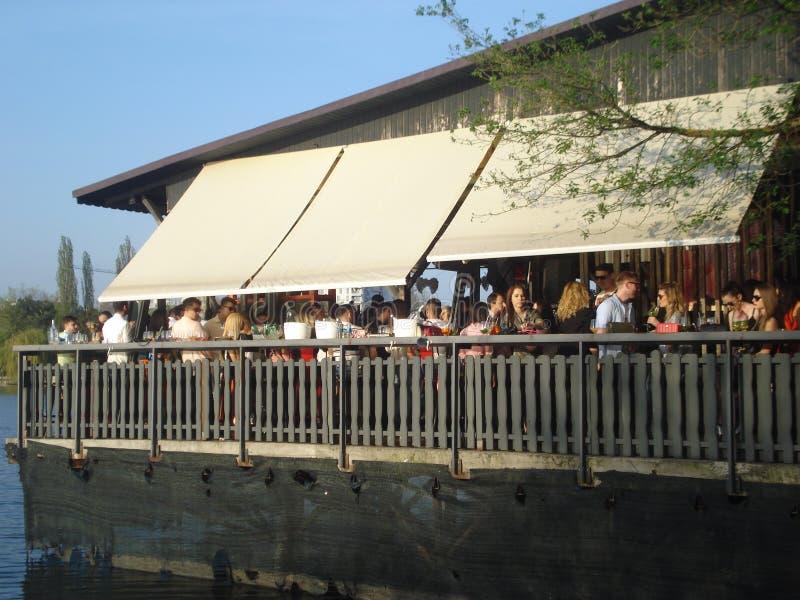 Les jeunes faisant la fête sur la terrasse extérieure sur le lac étayent photo libre de droits