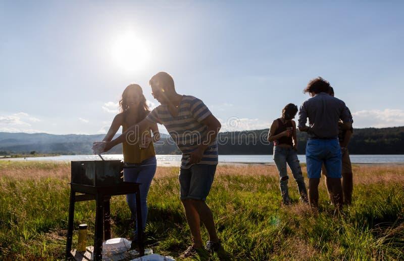 Les jeunes faisant le BBQ au pré de bord de lac photos libres de droits