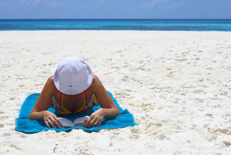 Les jeunes femmes affiche le livre sur la plage images libres de droits