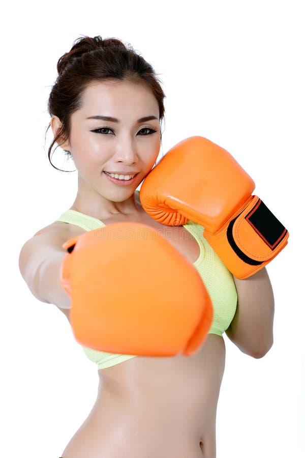 Les jeunes femmes asiatiques sexy amincissent l'ajustement portant la boxe orange de gant sur le wh image libre de droits