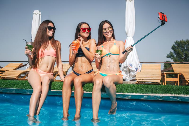 Les jeunes femmes bien baties et positives s'asseyent au bord de la piscine Ils posent et sourient Le modèle sur la droite prend  photographie stock libre de droits