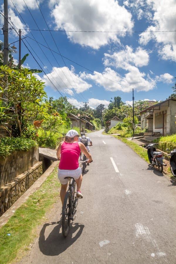 Les jeunes femmes fait du vélo pendant la visite cycloe de gisements de riz dans Bali photos libres de droits