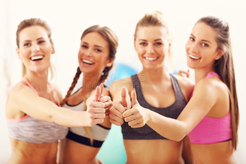 Les jeunes femmes groupent heureux au gymnase après séance d'entraînement image stock