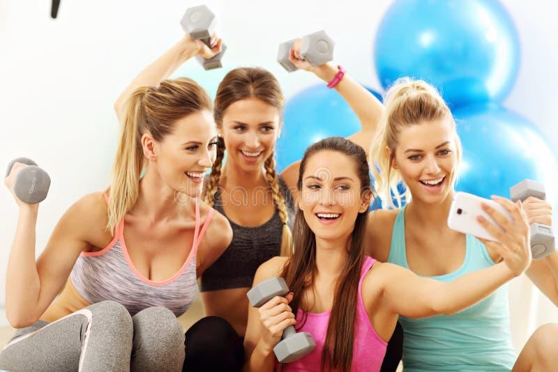 Les jeunes femmes groupent prendre le selfie au gymnase après séance d'entraînement image stock