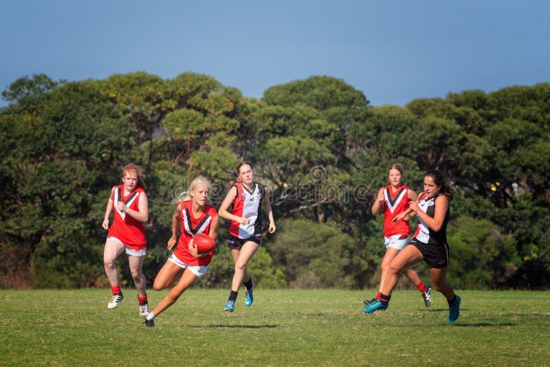 Les jeunes femmes jouent au football de r?gles d'Australien photographie stock libre de droits