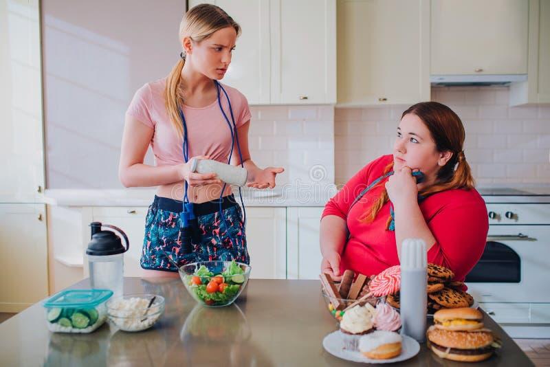 Les jeunes femmes minces et de poids excessif regardent l'un l'autre dans la cuisine Cuvette modèle mince de prise avec de la sal image stock