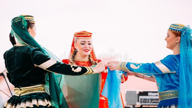 Les jeunes femmes se sont habillées dans des costumes traditionnels de gens dansant l'Azerbaïdjanais photo stock