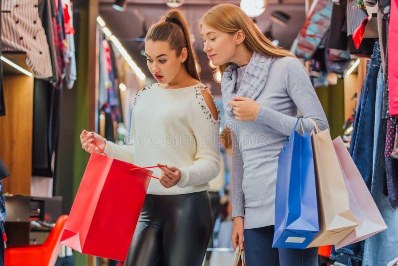 Les jeunes filles achetant beaucoup de choses dans le magasin gardent des sacs à provisions photographie stock libre de droits