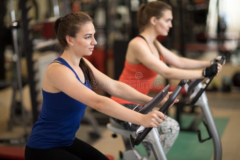 Les jeunes filles attirantes dans l'habillement de sports s'exerçant sur le gymnase va à vélo photo stock