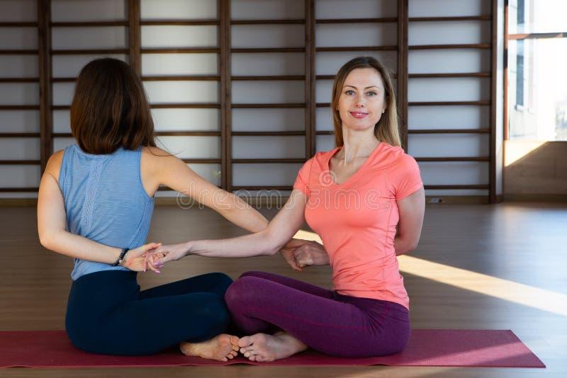 Les jeunes filles attirantes de sport font le yoga ensemble formation de groupe images stock
