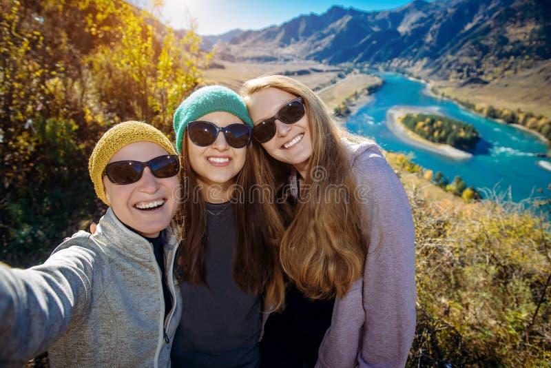 Les jeunes filles europian drôles dans des lunettes de soleil contre le paysage de montagne font le selfie, le voyage de famille  photo libre de droits