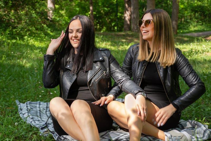 Les jeunes filles heureuses parlant en nature et s'asseyant dans le pré sur une couverture, filles rient et apprécient une belle  image libre de droits