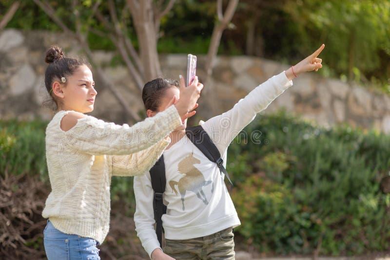 Les jeunes filles prennent une photo avec le smartphone extérieur photo stock