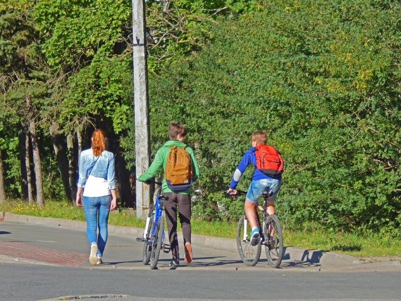 Les jeunes font un tour avec leurs bicyclettes photographie stock