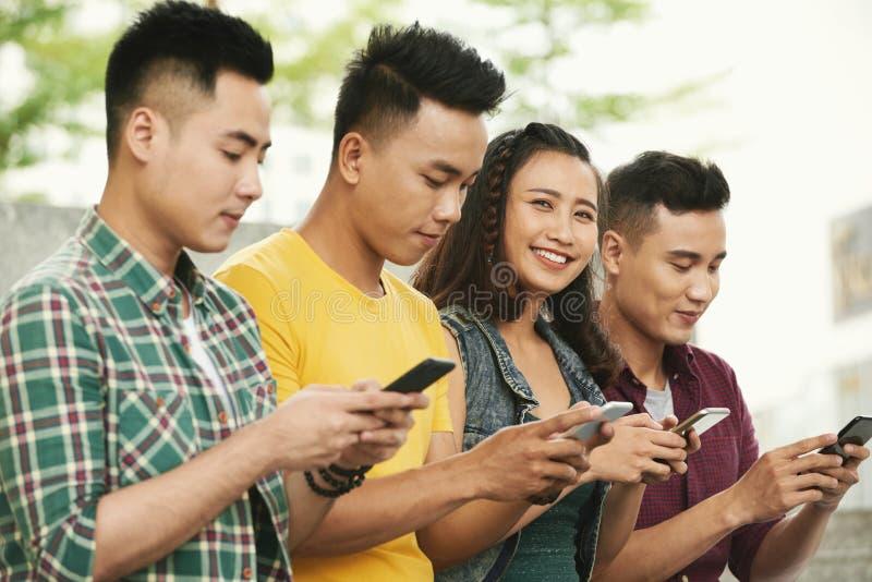 Les jeunes gais avec des smartphones image stock