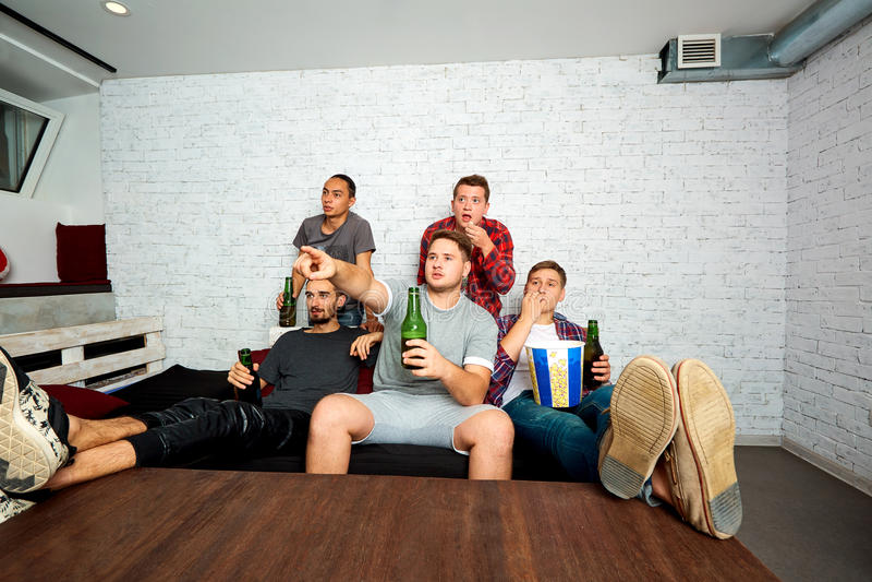 Les jeunes garçon-fans regardent la TV, détendent, ont l'amusement et boivent de la bière ami photo libre de droits