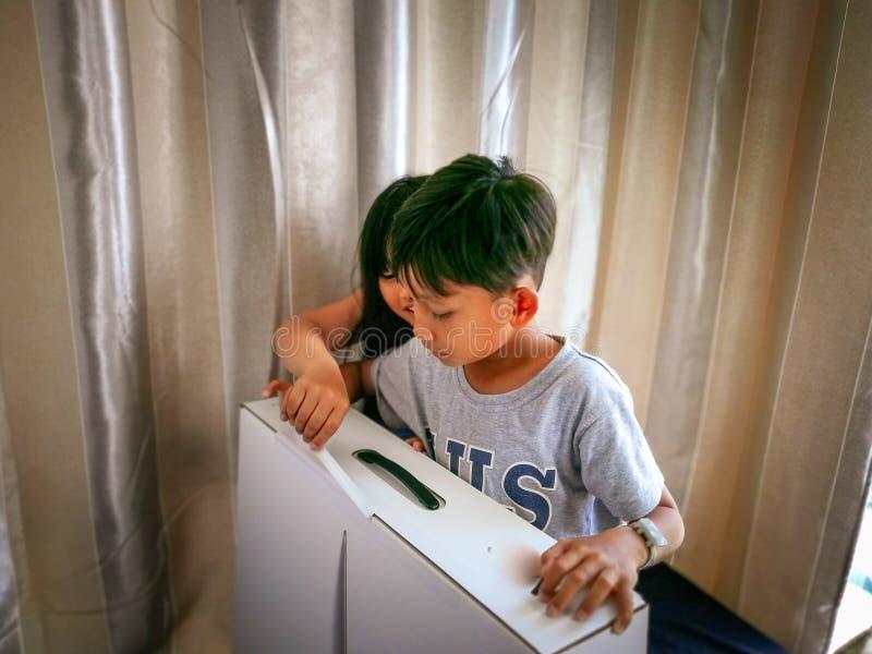 Les jeunes garçons excités avec l'article ont acheté en ligne unboxed à la maison photos stock