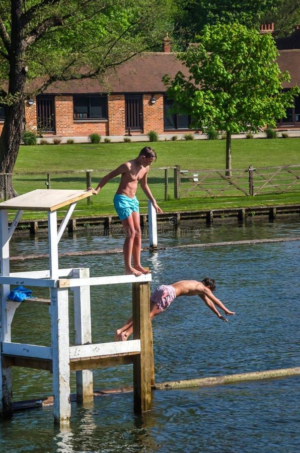 Les jeunes garçons heureux sautent dedans à la Tamise près de la ville Henley dans Oxfordshire image stock